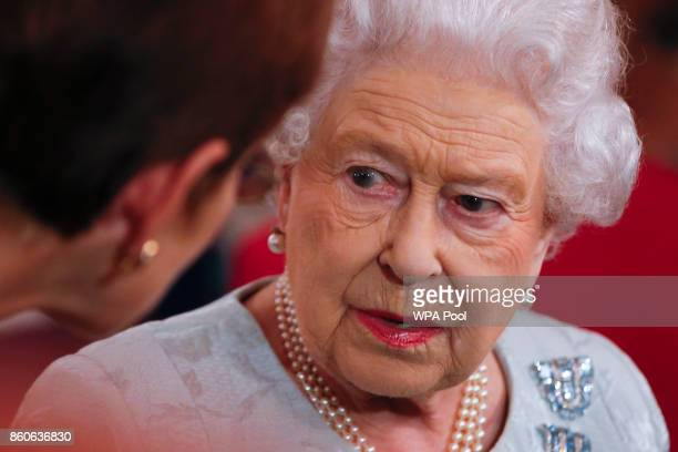 Queen Elizabeth II talks to guests during a reception to celebrate the Women's Royal Naval Service 100 project at The Army and Navy Club on October...