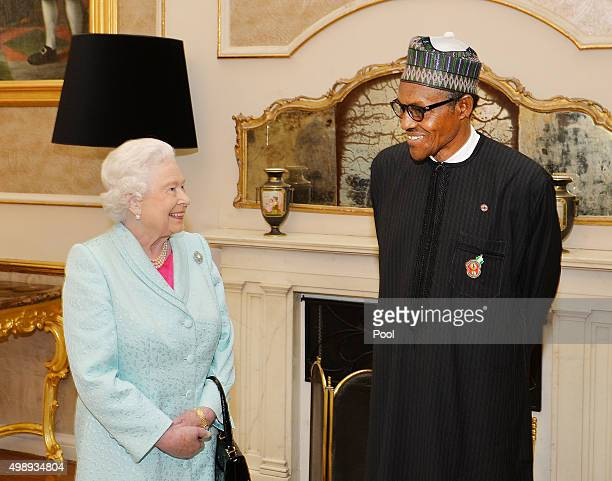 Queen Elizabeth II talks to President Muhammadu Buhari of Nigeria during a Heads of Government reception at the San Anton Palace on November 27 2015...