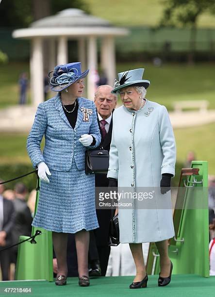 Queen Elizabeth II talks to Sarah Goad as the Magna Carta Commemoration Monument is seen in the background at a Magna Carta 800th Anniversary...