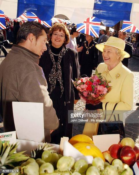 Queen Elizabeth II talks to stallholder Adrian Prince during he tour of the market square in Enfield Town centre London During the visit to the...