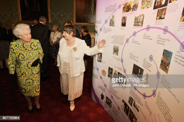 Queen Elizabeth II talks with Adele Smith author of a book on the history of the Royal OverSeas League as she shows a timeline of the organisation's...