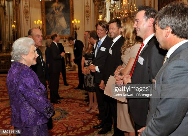 Queen Elizabeth II talks with Elle Macpherson and Craig Revel Horwood in the white drawing room at Buckingham Palace before a Royal reception for...