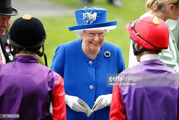 Queen Elizabeth II talks with jockeys Jamie Spencer and Sean Levey prior to them riding her horses 'Touchline' and 'Pack Together' in The Sandringham...