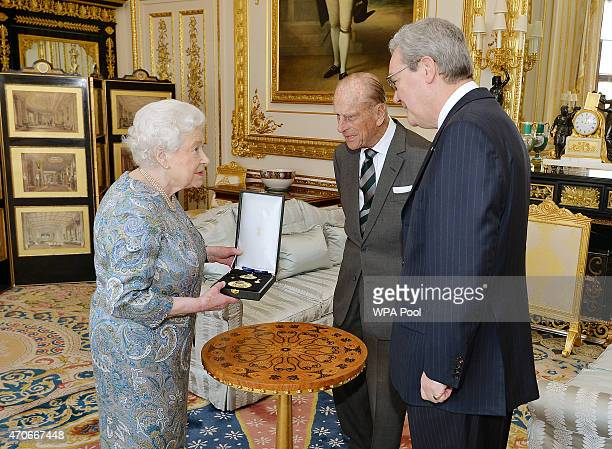 Queen Elizabeth II talks with the Australian High Commissioner Alexander Downer as she prepares to present the Prince Philip Duke of Edinburgh with...