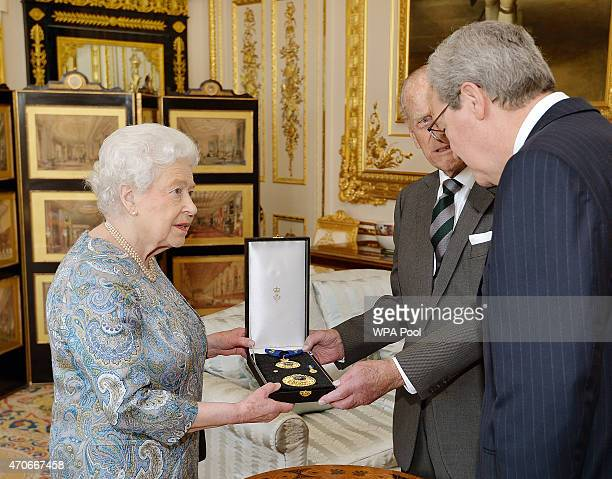 Queen Elizabeth II talks with the Australian High Commissioner Alexander Downer as she presents the Prince Philip Duke of Edinburgh with the Insignia...