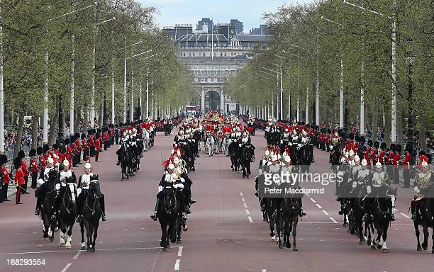 Queen Elizabeth II travels by coach on The Mall as she returns to Buckingham Palace after the State Opening of Parliament on May 8 2013 in London...