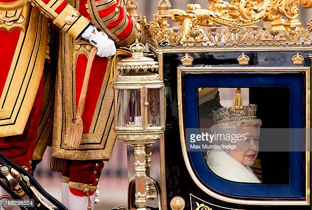 Queen Elizabeth II travels in a horse drawn carriage from Buckingham Palace to attend the State Opening of Parliament on May 8 2013 in London England...