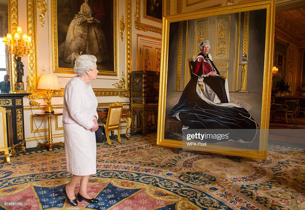 Queen Elizabeth II views a portrait of herself by British artist Henry Ward, marking six decades of patronage to the British Red Cross, which has been unveiled at Windsor Castle on October 14, 2016 in Windsor, England. The Queen is the longest-serving patron of the charity, which supports people in crisis in the UK and overseas.