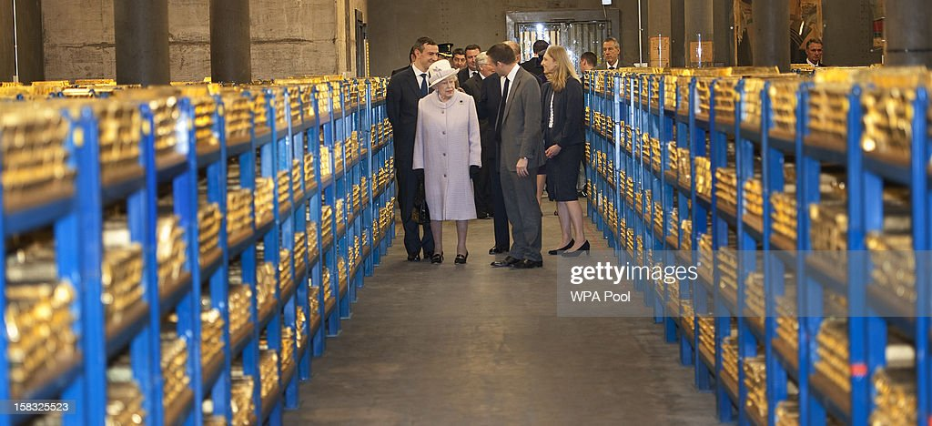 Queen Elizabeth II views stacks of gold as she visits the Bank of England with <a gi-track='captionPersonalityLinkClicked' href=/galleries/search?phrase=Prince+Philip&family=editorial&specificpeople=92394 ng-click='$event.stopPropagation()'>Prince Philip</a>, Duke of Edinburgh on December 13, 2012 in London, England. Governor, Sir Mervyn King met with the Queen and Duke before they visited the Banking Hall to discuss payment system controls. The royal couple viewed banknotes, counterfeit currency, a gold vault, historical items, met with gold experts, security staff and the Market Operations Office while on their visit to the Bank of England.