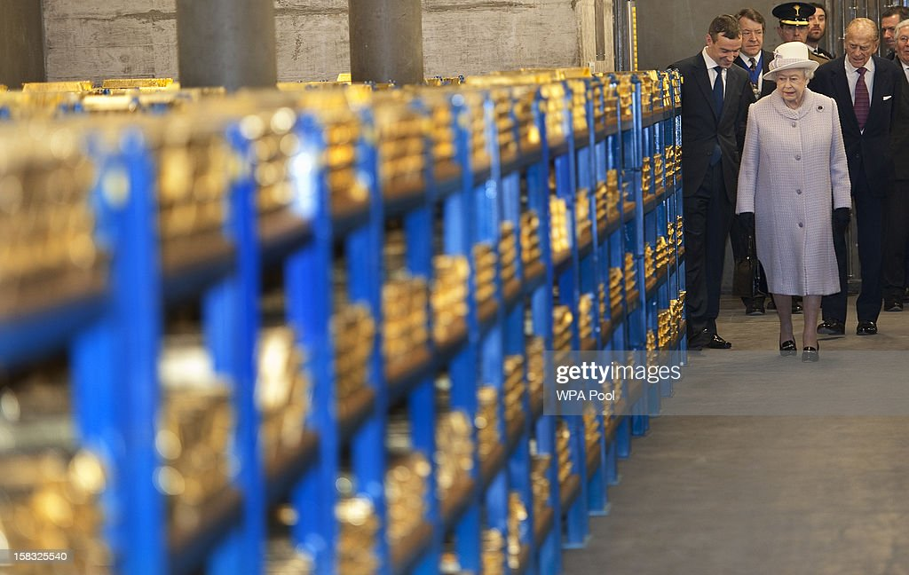 Queen Elizabeth II views stacks of gold as she visits the Bank of England with Prince Philip, Duke of Edinburgh on December 13, 2012 in London, England. Governor, Sir Mervyn King met with the Queen and Duke before they visited the Banking Hall to discuss payment system controls. The royal couple viewed banknotes, counterfeit currency, a gold vault, historical items, met with gold experts, security staff and the Market Operations Office while on their visit to the Bank of England.