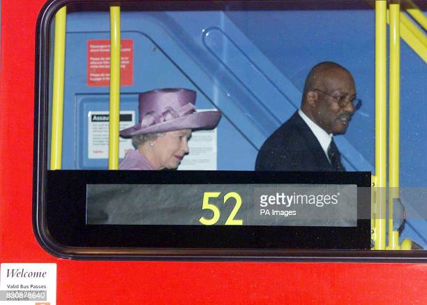 Queen Elizabeth II walks through a double decker bus with driver Eugene Collymore at Willesden bus garage North London The Queen was seeing the...