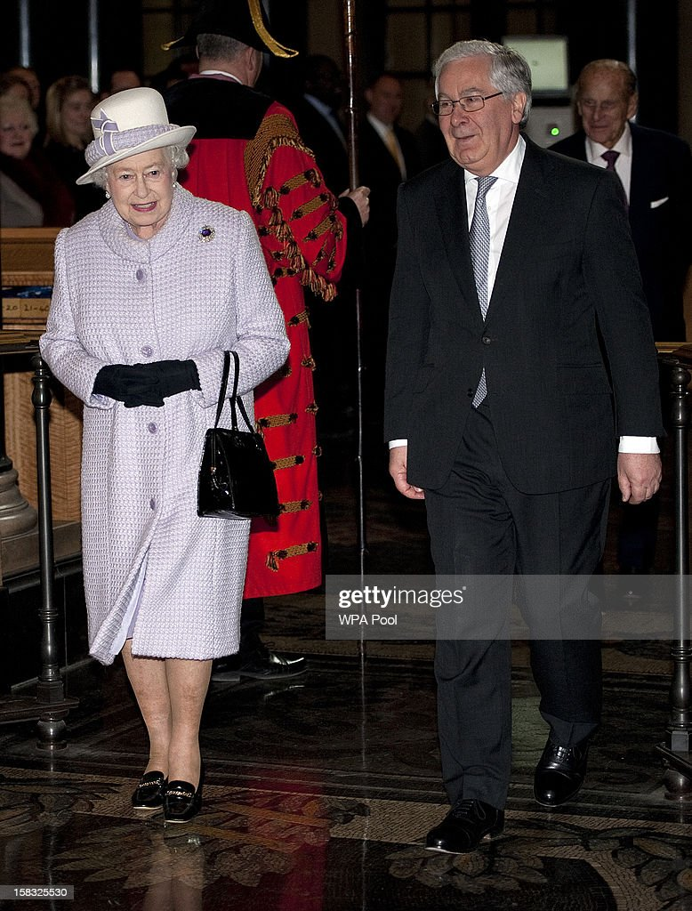 Queen Elizabeth II walks with Governor, Sir Mervyn King as she visits the Bank of England with Prince Philip, Duke of Edinburgh on December 13, 2012 in London, England. Governor, Sir Mervyn King met with the Queen and Duke before they visited the Banking Hall to discuss payment system controls. The royal couple viewed banknotes, counterfeit currency, a gold vault, historical items, met with gold experts, security staff and the Market Operations Office while on their visit to the Bank of England.