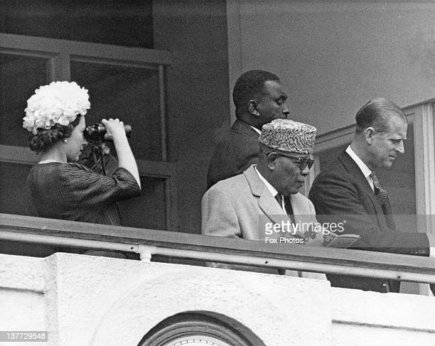 Queen Elizabeth II watching the Derby through binoculars from the Royal Box at Epsom Downs Racecourse Surrey 3rd June 1964 With her is President...