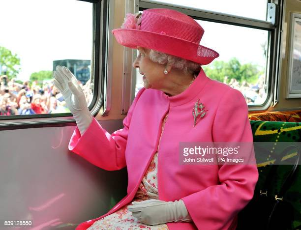 Queen Elizabeth II waves as she and the Duke of Edinburgh get off an electric Tram after a short journey through the Melbourne city centre past huge...