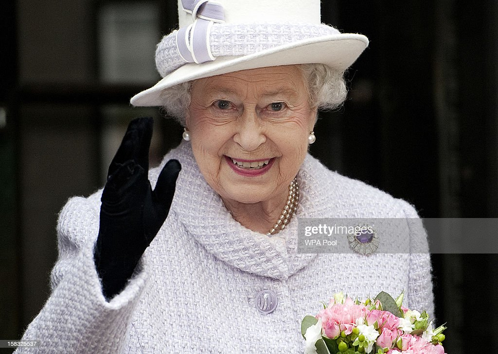 Queen Elizabeth II waves as she visits the Bank of England with Prince Philip, Duke of Edinburgh on December 13, 2012 in London, England. Governor, Sir Mervyn King met with the Queen and Duke before they visited the Banking Hall to discuss payment system controls. The royal couple viewed banknotes, counterfeit currency, a gold vault, historical items, met with gold experts, security staff and the Market Operations Office while on their visit to the Bank of England.