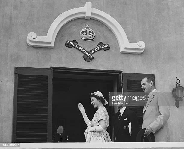 Queen Elizabeth II waves at the crowds as she visits the Royal Bermuda Yacht Club Bermuda during her Commonwealth Tour 24th November 1954 Behind her...