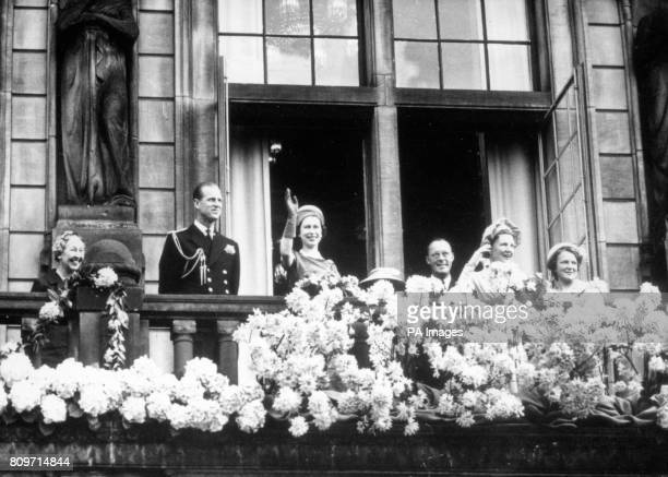 Queen Elizabeth II waves from the balcony of Rotterdam Town Hall to the crowds which gathered outside On the balcony with the Queen are the Duke of...