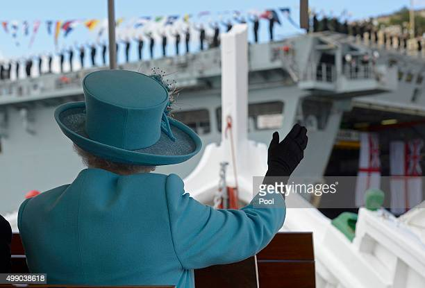 Queen Elizabeth II waves to British Royal Navy crew members performing a salute on the HMS Bulwark amphibious assault ship during a tour of the Grand...