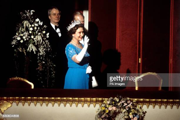 Queen Elizabeth II waves to the audience from the Royal Box on her arrival inside the Royal Opera House Covent Garden London as part of her 60th...