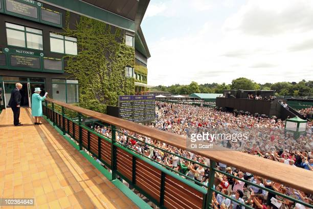 Queen Elizabeth II waves to the crowds as she attends the Wimbledon Lawn Tennis Championships on Day 4 at the All England Lawn Tennis and Croquet...
