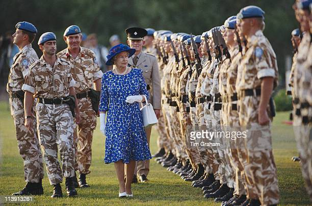 Queen Elizabeth II wearing a blue and white dress with a blue hat as she inspects UN peacekeeping troops during a visit to Cyprus 21 October 1993 The...