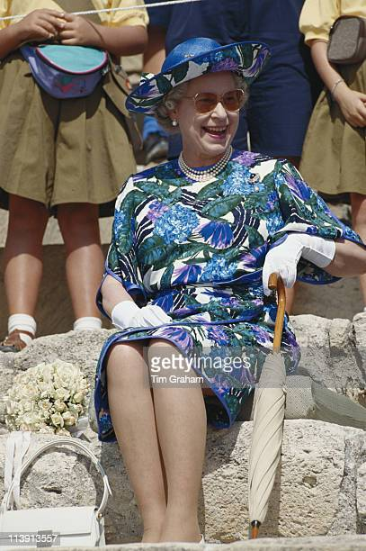 Queen Elizabeth II wearing a blue multicoloured dress designed by John Anderson and a hat by milliner Philip Somerville sitting laughing during a...