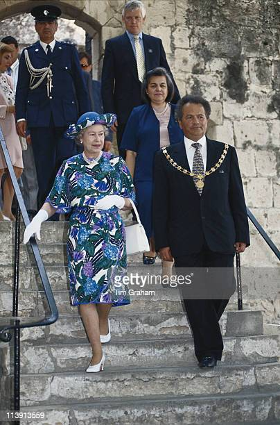 Queen Elizabeth II wearing a blue multicoloured dress designed by John Anderson and a hat by milliner Philip Somerville on a walkabout with local...