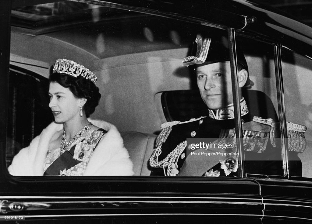 Queen Elizabeth II wearing a crown and jewels rides with Prince Philip Duke of Edinburgh as they make their way from Buckingham Palace to Lancaster...