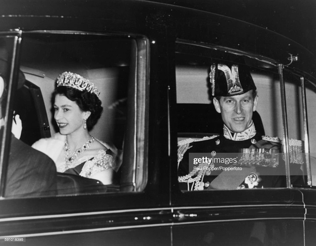 Queen Elizabeth II wearing a crown and jewels rides with Prince Philip Duke of Edinburgh as they arrive back at Buckingham Palace after attending a...