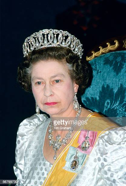 Queen Elizabeth II wearing a diamond and pearl circle tiara with the jubilee necklace at a state banquet during her official visit to Nepal