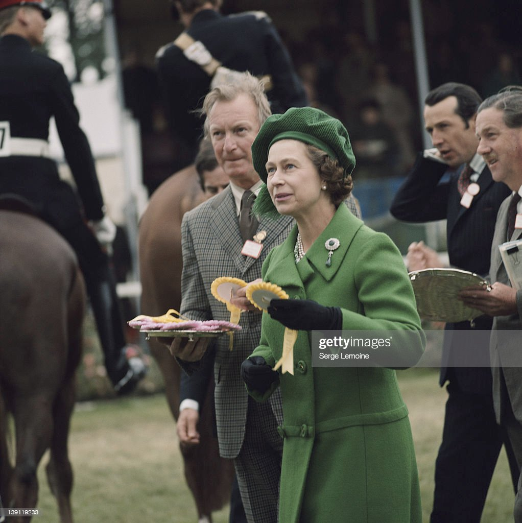 Queen <a gi-track='captionPersonalityLinkClicked' href=/galleries/search?phrase=Elizabeth+II&family=editorial&specificpeople=67226 ng-click='$event.stopPropagation()'>Elizabeth II</a>, wearing a green coat and matching hat, awards rosettes at the Royal Windsor Horse Show, held at Home Park in Windsor, Berkshire, England, Great Britain, circa 1980.