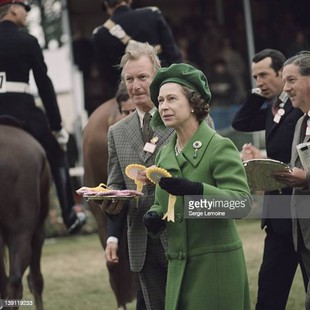 Queen Elizabeth II wearing a green coat and matching hat awards rosettes at the Royal Windsor Horse Show held at Home Park in Windsor Berkshire...