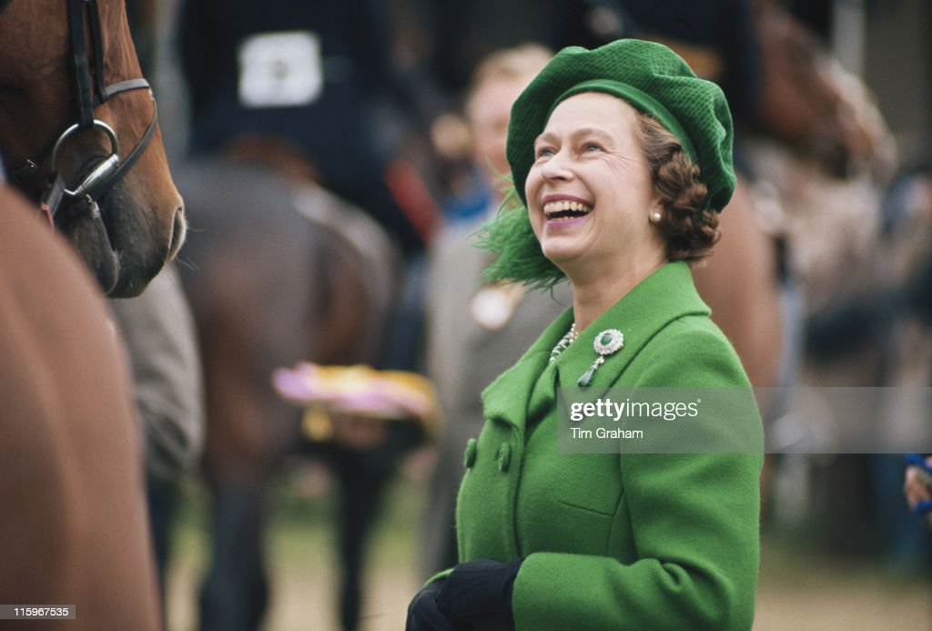 Queen Elizabeth II Wearing A Green Coat And Matching Hat Laughing As She Attends