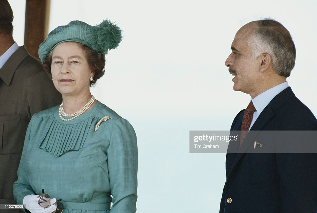 Queen <a gi-track='captionPersonalityLinkClicked' href=/galleries/search?phrase=Elizabeth+II&family=editorial&specificpeople=67226 ng-click='$event.stopPropagation()'>Elizabeth II</a>, wearing a hat designed by Simone Mirman, standing beside <a gi-track='captionPersonalityLinkClicked' href=/galleries/search?phrase=King+Hussein&family=editorial&specificpeople=93663 ng-click='$event.stopPropagation()'>King Hussein</a> of Jordan (1935-1999) during a state visit to Jordan, in March 1984.