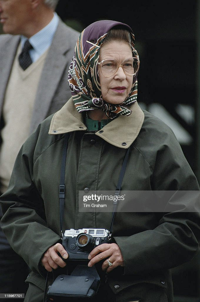 Queen Elizabeth II Wearing A Headscarf And Green Waxed Jacket Holding Leica
