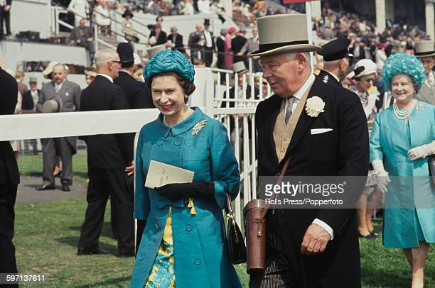 Queen Elizabeth II wearing a light blue coat and hat is escorted by Bernard FitzalanHoward 16th Duke of Norfolk at the Epsom Derby race meeting at...