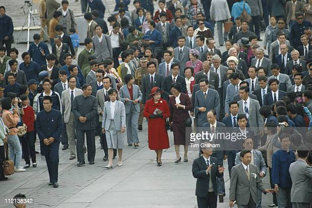 Queen Elizabeth II wearing a red coat walks among the crowds gathered in Beijing during her official State Visit to China October 1986 Prince Philip...