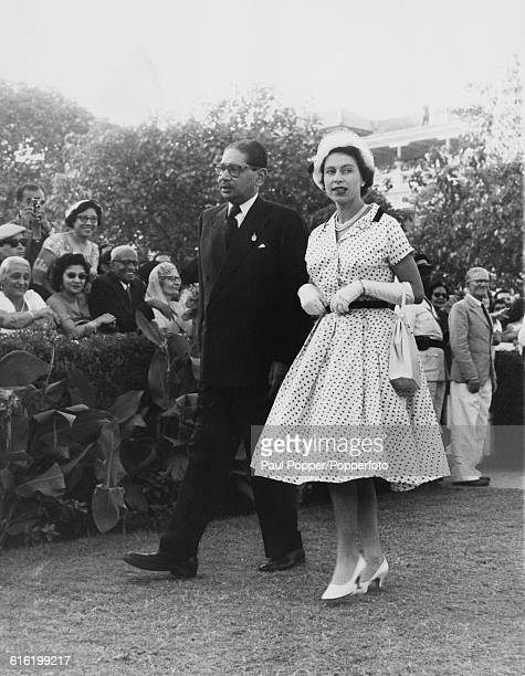 Queen Elizabeth II wearing a white dress with blue polka dots is escorted on a visit to Bombay racecourse during the Queen's tour of India on 25th...