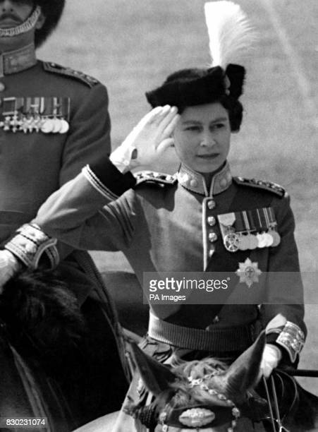 Queen Elizabeth II wearing her uniform as ColonelinChief of the Grenadier Guards takes the salute at the gates of Buckingham Palace as the Guards...