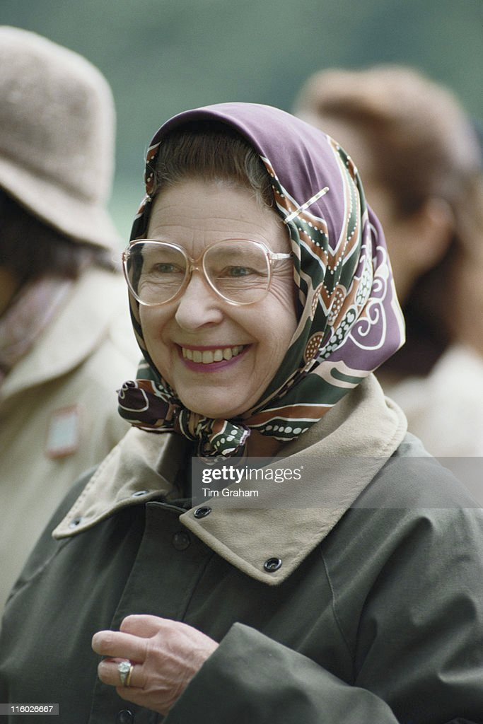 Queen Elizabeth II Wearing Spectacles A Headscarf And Green Waxed Jacket Smiling At