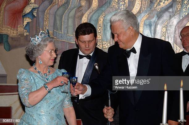 Queen Elizabeth II wearing the Brazilian Aquamarine Parure Tiara and President Boris Yeltsin raise their glasses to each other during a State Banquet...