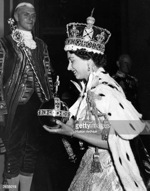 Queen Elizabeth II wearing the Imperial state Crown and carrying the Orb and sceptre leaving the state coach and entering Buckingham Palace after the...