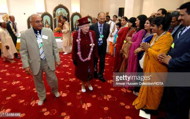 Queen Elizabeth II wears slippers and is presented with a garland when she visits a new Hindu Temple in Bradford on May 24 2007