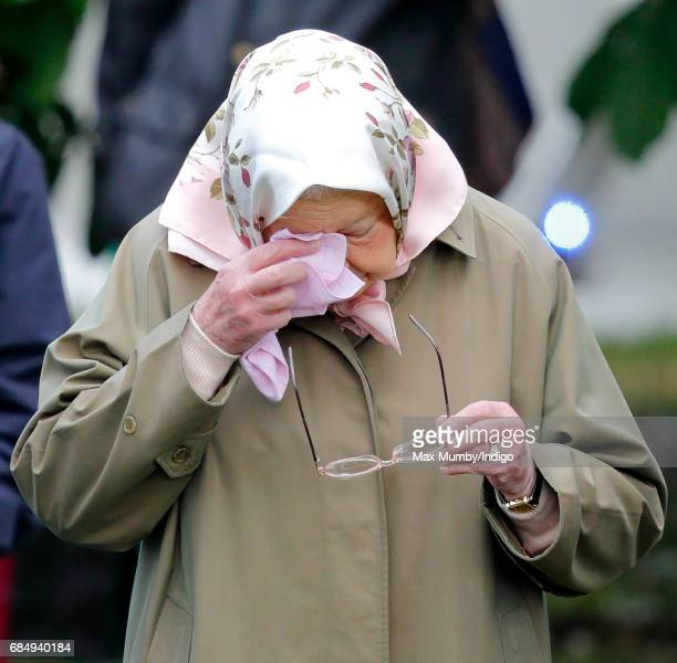Queen Elizabeth II wipes her eyes as she watches her horse 'Balmoral Angel' compete in the Highland Class on day 3 of the Royal Windsor Horse Show in...