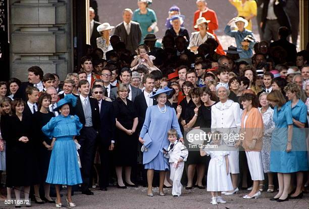 Queen Elizabeth II With Her Arm Around Her Grandson Prince William As With Other Members Of The Royal Family And Household Staff In The Forecourt Of...