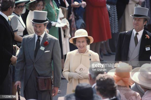 Queen Elizabeth II with her bodyguard Commander Michael Trestrail and the Marquis of Abergavenny walking through the crowds at the Royal Ascot race...