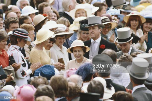 Queen Elizabeth II with her bodyguard Commander Michael Trestrail walking through the crowds at the Royal Ascot race meeting at Ascot racecourse in...