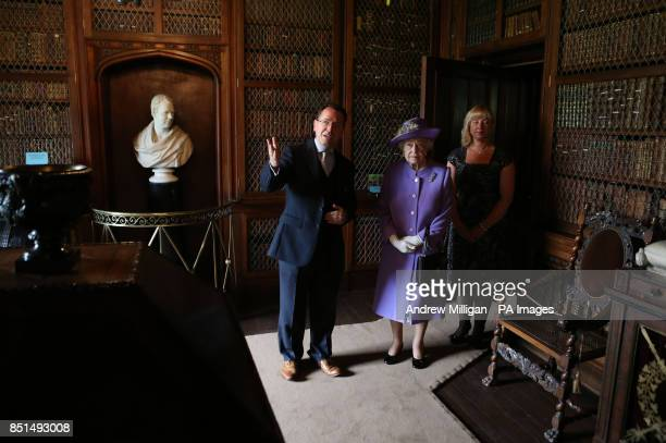 Queen Elizabeth II with Jason Dyer and Beverley Rutherford from the Abbotsford Trust during a tour of Abbotsford House the home of Sir Walter Scott...