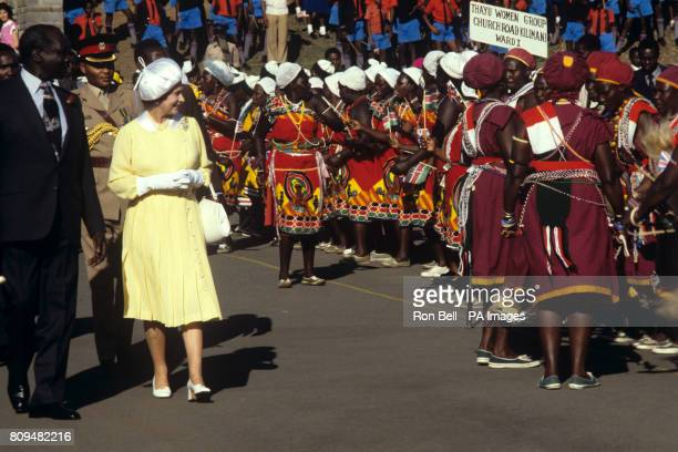 Queen Elizabeth II with Kenyan President Daniel Arap Moi is greeted by tribal dancers at Jomo Kenyatta International Airport