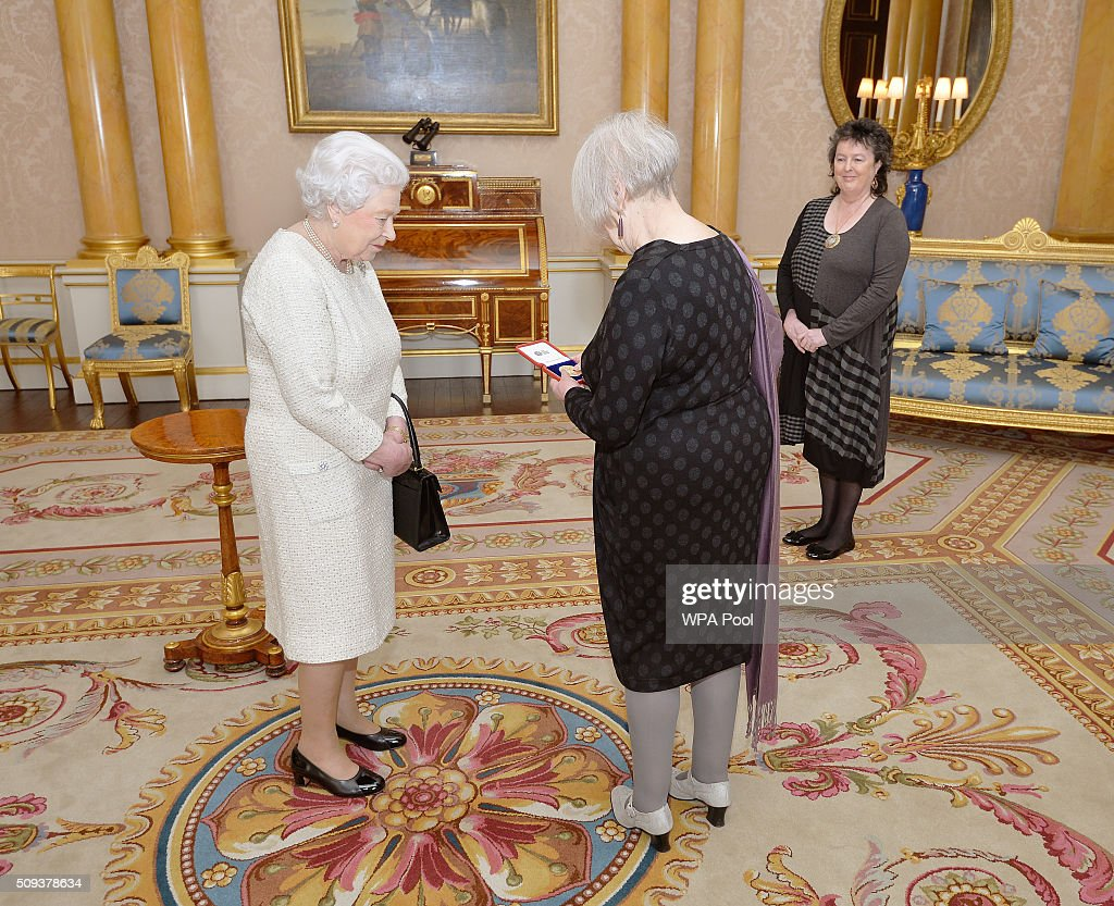 Queen Elizabeth II with Liz Lochhead after she presentd her with the Queen's Gold Medal for Poetry, accompanied by Poet Laureate Professor Dame Carol Ann Duffy during a private audience, at Buckingham Palace in Westminster on February 10, 2016 in London, England.